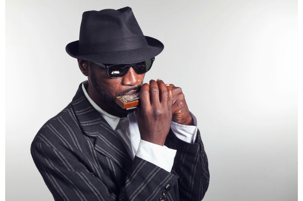 Man in a suit and hat playing blues harmonica