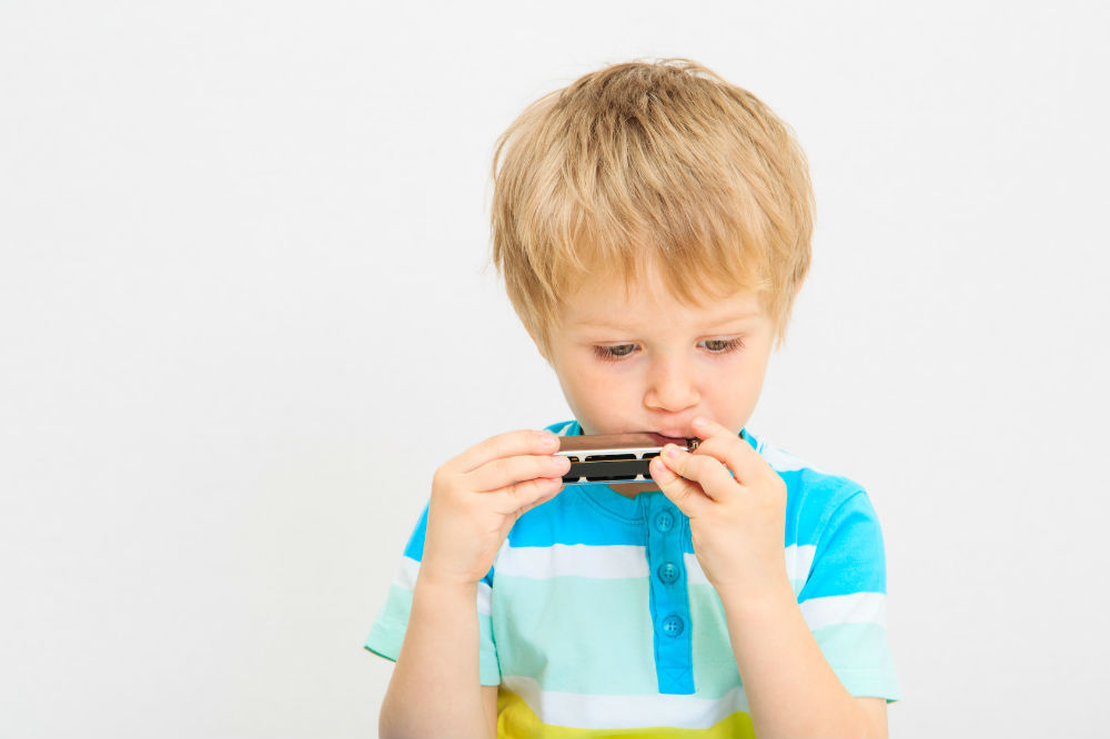 a toddler playing one of the best harmonicas for kids