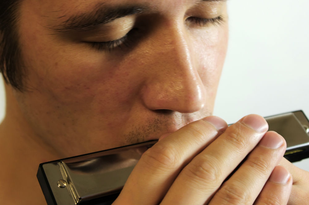 Close up of someone playing the Hohner harmonica