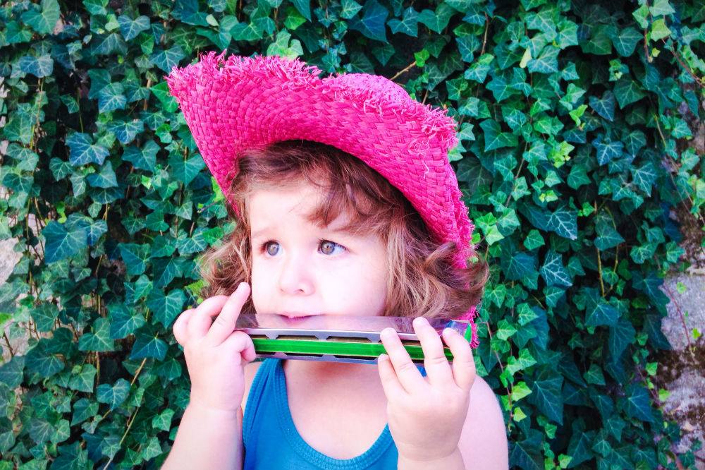 A little girl playing the Hohner Special 20 Harmonica