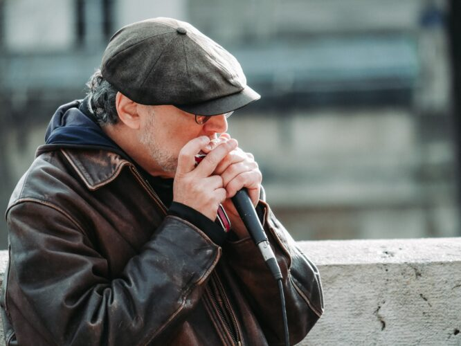 Man in a hat playing harmonica into a mic