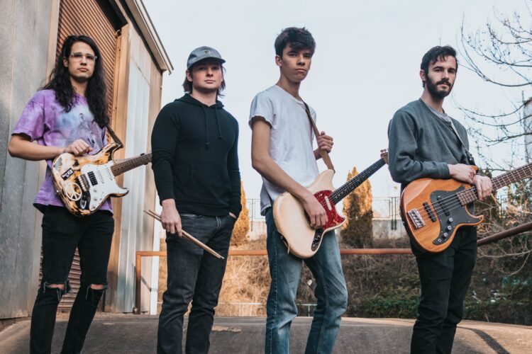 a 4 person rock band standing outside and holding their instruments