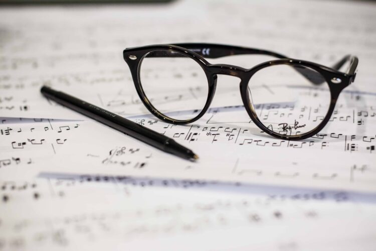black glasses and pen sitting on sheet music