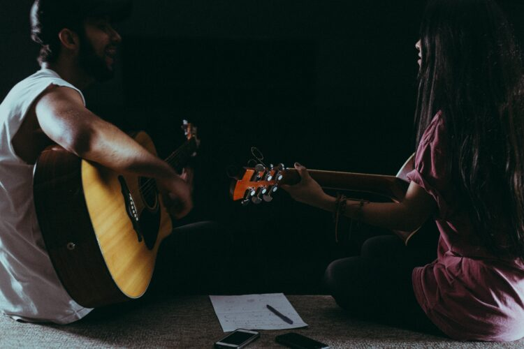 two people playing guitar and facing each other