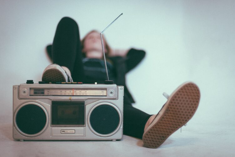 Man laying down with one foot up on silver stereo