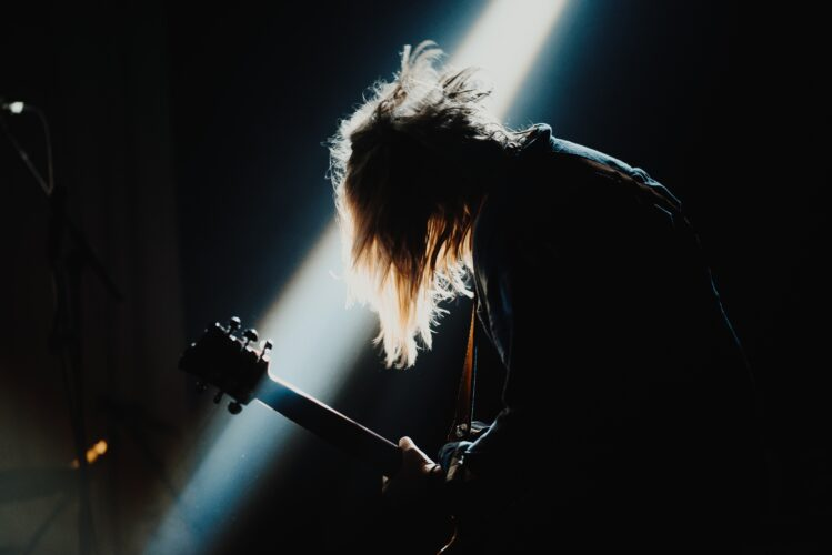 A person playing rock music on electric guitar