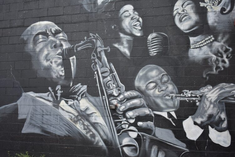 mural of blues musicians on a brick wall in black and white