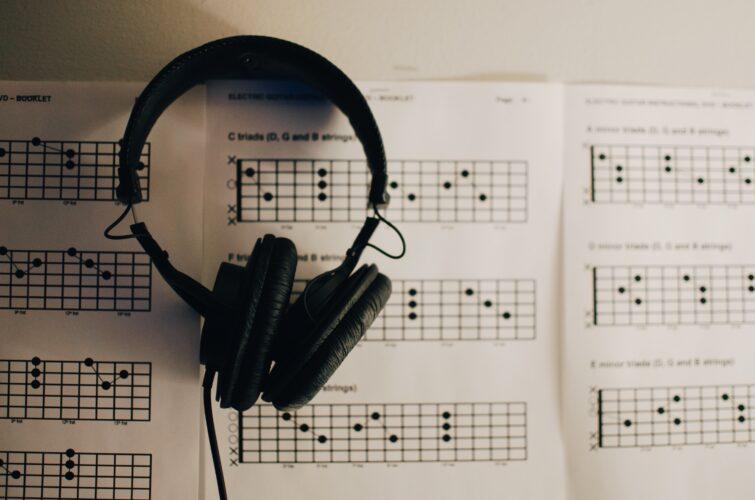 Black headphones on top of a guitar chords book