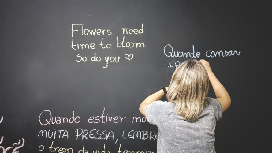 A blonde person writing quotes on a chalk board in multiple languages