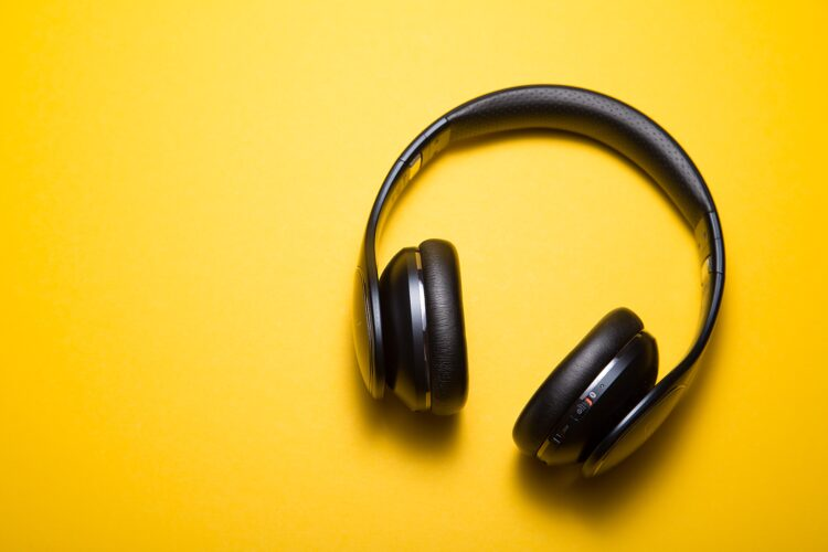 A pair of black, over ear headphones on a yellow background