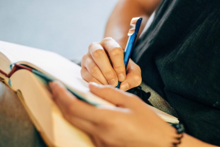 A person holding a notebook and taking notes