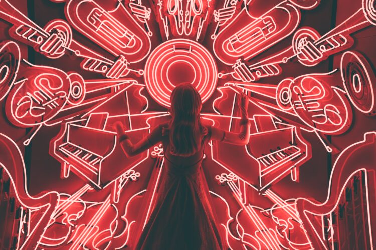 A person facing red neon lights of all kinds of instruments