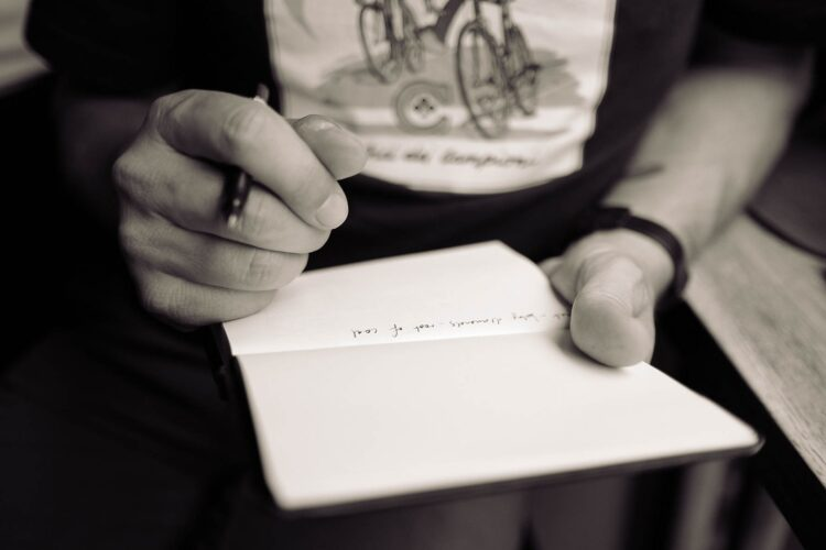 A Man with a notebook and a pen writing songs